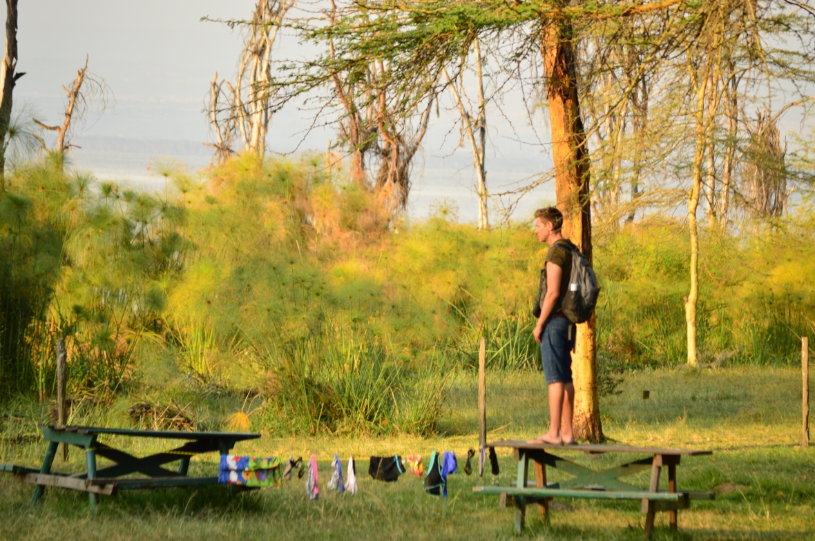 Camper Chris observing hippos from atop a picnic table at Lake Naivasha campground in Kenya